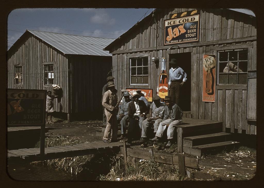 """Migratory laborers outside of a """"juke joint"""" during a slack season"""
